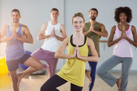 performing: Group of people performing yoga in gym