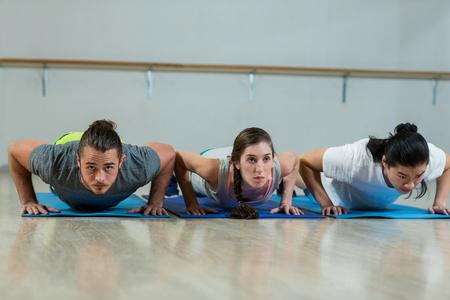 push ups: Group of fitness team doing push ups in fitness studio