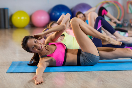 laying abs exercise: Group of women exercising in gym