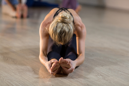 performing: Woman performing stretching exercise in fitness studio