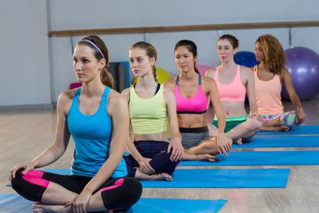 Grupo de mujeres que realizan yoga en el gimnasio
