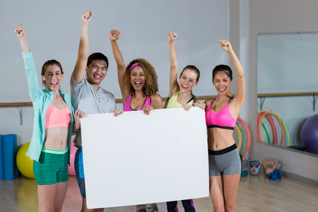 clenching fists: Portrait of group fitness team holding blank placard and clenching fists in fitness studio