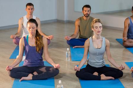 istruzione: Gruppo di persone che svolgono yoga in palestra
