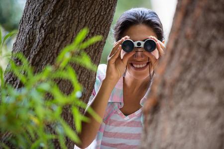 Female hiker looking through binoculars in forest Stock Photo