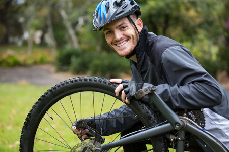 break chain: Portrait of smiling male cyclist repairing his mountain bike in park Stock Photo