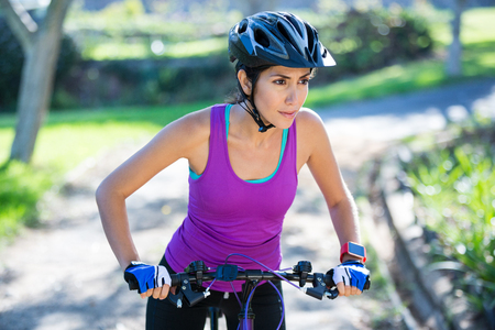 adventuring: Female cyclist cycling in countryside on sunny day