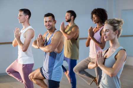 performing: Group of people performing yoga