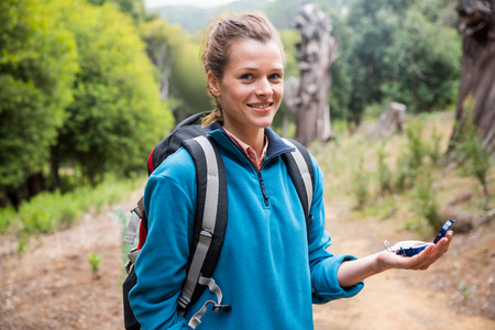 adventuring: Portrait of smiling female hiker holding compass in forest