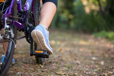 adventuring: Low section of female cyclist cycling in countryside