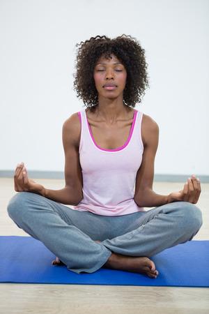 siddhasana: Woman doing meditation on exercise mat in fitness studio Stock Photo