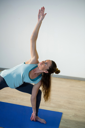 side angle pose: Woman performing extended side angle pose on exercise mat in fitness studio