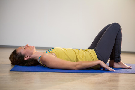 performing: Woman performing yoga exercise in fitness studio