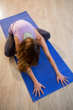 legged: Woman doing cross legged forward fold on exercise mat in fitness studio