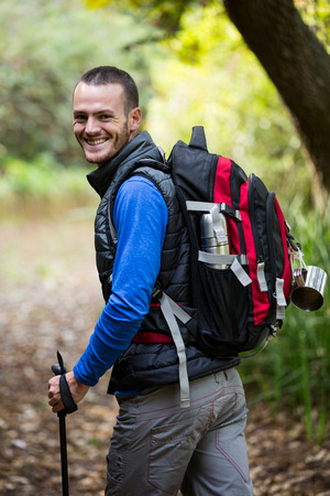 walking pole: Portrait of smiling male hiker walking with hiking pole in forest Stock Photo