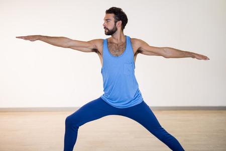 warrior pose: Man performing warrior pose in fitness studio