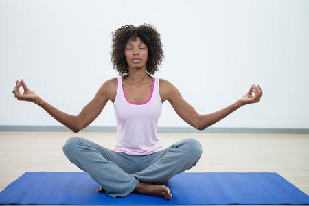 Woman doing meditation on exercise mat in fitness studio Stock Photo
