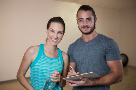 adult  body writing: Portrait of smiling fitness trainer and woman in fitness studio
