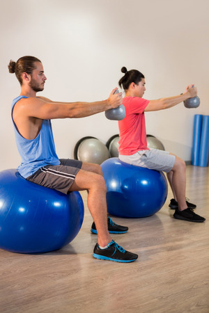 ball stretching: Men performing stretching exercise on exercise ball in gym