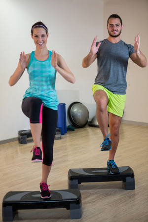 step fitness: Smiling man and woman doing step aerobic exercise on stepper in fitness studio Stock Photo