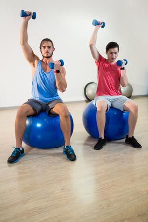 hombres haciendo ejercicio: Men exercising with dumbbells on exercise ball in gym