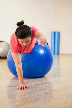 hombres haciendo ejercicio: Los hombres que ejercitan en la pelota de ejercicio en el gimnasio