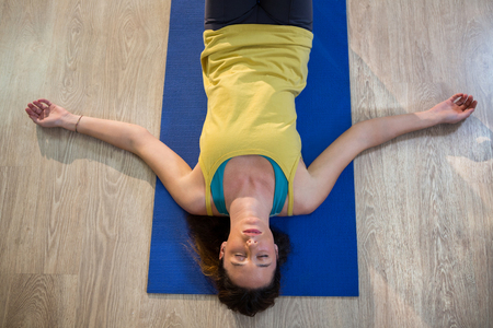 corpse: Woman doing yoga corpse pose on exercise mat in fitness studio Stock Photo