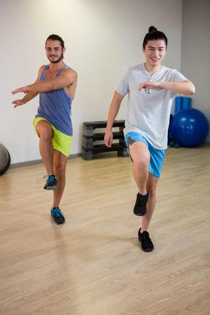 Retrato de dos hombres haciendo ejercicio aeróbico en el gimnasio
