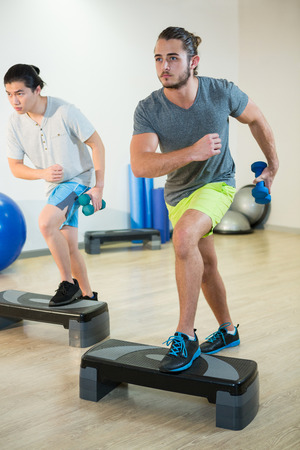step fitness: Two men doing step aerobic exercise with dumbbell on stepper in fitness studio