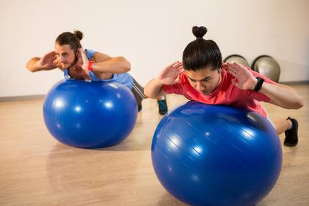 men exercising: Los hombres que ejercitan en la pelota de ejercicio en el gimnasio