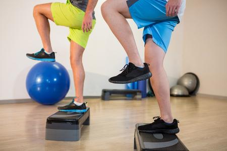 ejercicio aeróbico: Dos hombres que hacen ejercicio aeróbico paso en paso a paso en el estudio de la aptitud