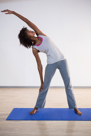 Woman performing yoga in gym