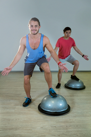hombres haciendo ejercicio: Los hombres que ejercitan en la bosuball en el gimnasio