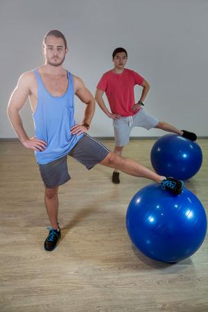 hombres haciendo ejercicio: Retrato de los hombres que ejercitan con la bola del ejercicio en el gimnasio