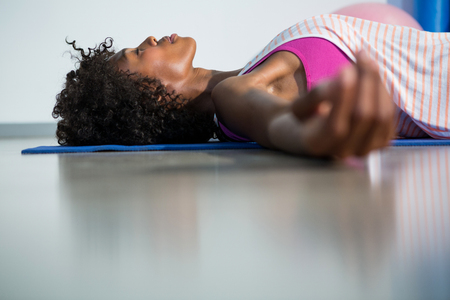 corpse: Woman in yoga corpse pose in gym Stock Photo