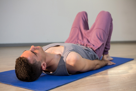 corpse: Man in yoga corpse pose in gym