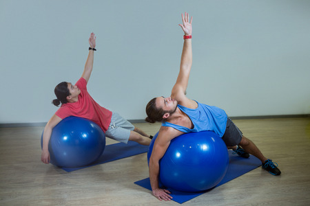 hombres haciendo ejercicio: Men exercising with exercise ball in gym Foto de archivo