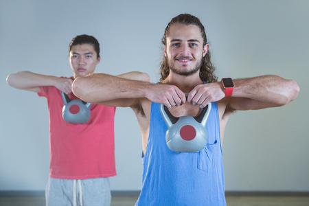 hombres haciendo ejercicio: Los hombres que ejercitan con pesas rusas en el gimnasio