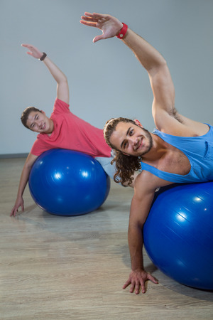 hombres haciendo ejercicio: Portrait of happy men exercising with exercise ball in gym