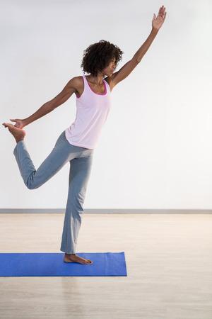 performing: Woman performing yoga in gym