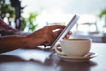 Hands of man using digital tablet in cafeteria Stock Photo