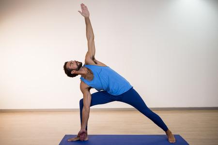 performing: Man performing yoga in gym