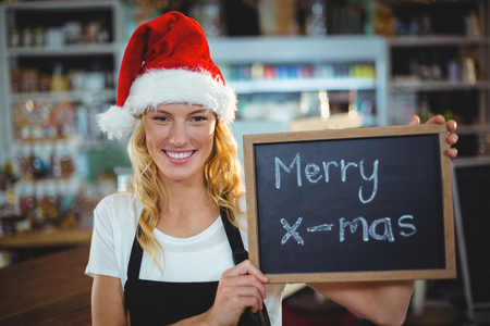 Portrait of smiling waitress showing chalkboard with merry x-mas sign in café