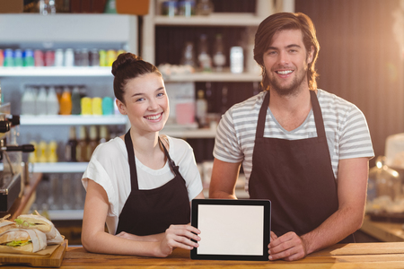 Smiling waiter and waitress using digital tablet at counter in café Stock Photo