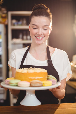 tempted: Smiling waitress holding dessert on cake stand in cafe