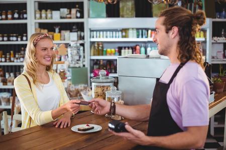 tomando refresco: dando la tarjeta de crédito del cliente feliz con el camarero en la cafetería