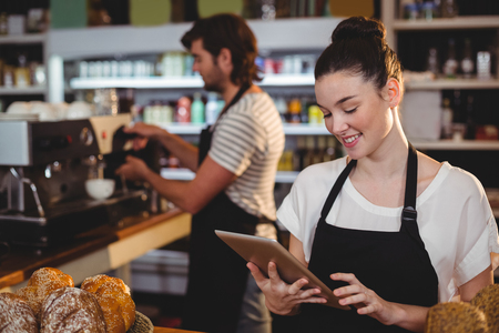 Smiling waitress standing at counter using digital tablet in cafe