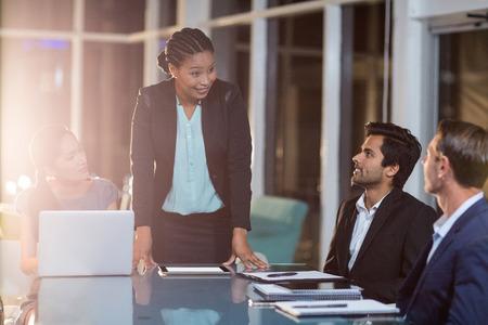 会議室での会議で同僚とやり取りする実業家