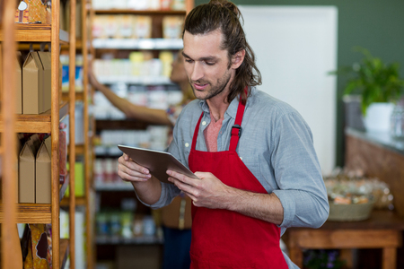 Male staff using a digital tablet in supermarket Stock Photo