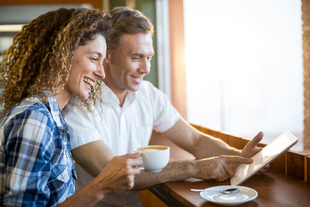 Happy couple using digital tablet while having coffee in a café Stock Photo