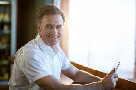 Portrait of smiling man using a digital tablet in café Stock Photo